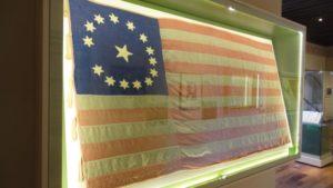 """Imagen 12. Museo Nacional de las Intervenciones. Sala """"La Guerra entre México y Estados Unidos, 2011"""". Registro propio. Al entrar a sala, la bandera Norteamerica recibe al visitante, en ella se observan 15 estrellas en círculo: las Trece Colonias, La Florida y La Luisiana. La estrella del centro representa Texas."""